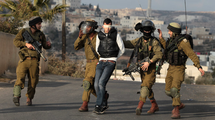 Israeli soldiers detain a Palestinian youth during clashes in the West Bank village of Silwad, north of Ramallah, on January 17, 2014 following a protest of Palestinians against the expansion of the nearby Israeli settlement of Ofra. (AFP Photo/Abbas Momani)