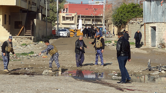 Iraqi security forces inspect the site of a bomb explosion in the northern Iraqi city of Kirkuk on January 18, 2014. (AFP Photo / Marwan Ibrahim)