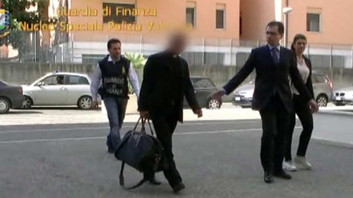 This handout picture taken from a video released by the Guardia di Finanzia Italian police on June 28, 2013 shows Nunzio Scarano (front-L) escorted by policemen after being arrested the same day in Rome.  (AFP/GUARDIA DI FINANZA)