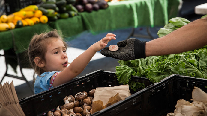 A girl pays for her mother's groceries using Electronic Benefits Transfer (EBT) tokens, more commonly known as Food Stamps, at the GrowNYC Greenmarket in Union Square on September 18, 2013 in New York City. (Andrew Burton/Getty Images/AFP)