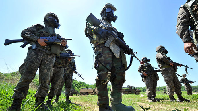 A US soldier (C) and South Korean soldiers wearing gas masks participate in a decontamination training conducted by US Army's 23rd Chemical Battalion at a military training field in Yeoncheon, northeast of Seoul, on May 16, 2013.(AFP Photo / Jung Yeon-Je)
