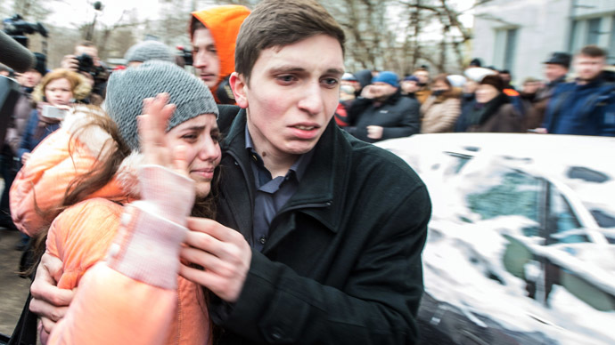 A schoolgirl (L) of school number 263 is hugged by her relative as she left the school building in Moscow on February 3, 2014. (AFP Photo/Dmitry Serebryakov)