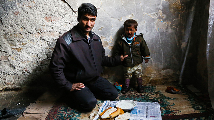 A Syrian man and his son sits for a lunch in an evacuated building on January 27, 2014 in the Kucukpazar district of Istanbul. (AFP Photo / Gurcan Ozturk)