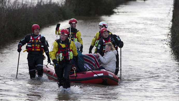 Devon and Somerset Fire and rescue service evacuate two women and two cats in baskets through flood waters in Burrowbridge on February 9, 2014. (AFP Photo / Justin Tallis)