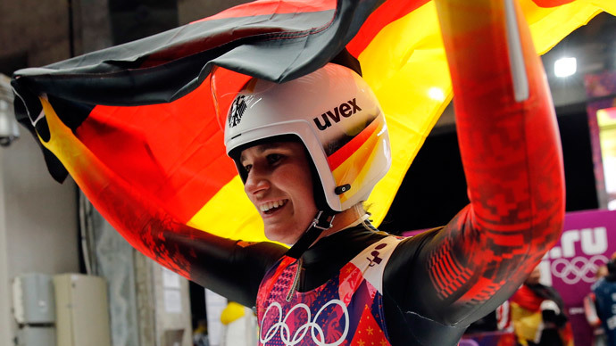 Germany's Natalie Geisenberger celebrates with a national flag after winning the women's luge singles competition during the 2014 Sochi Winter Olympics, February 11, 2014 (Reuters / Fabrizio Bensch)