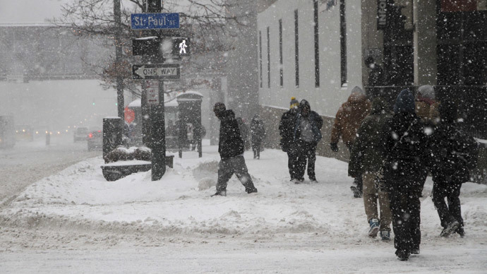 Pedestrians walk on Main Street during a snow storm on February 5, 2014 in Rochester, New York (AFP Photo / Guy Solimano)