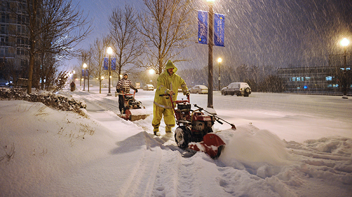 Workers use snow-blowers to clear snow from a sidewalk in Chevy Chase, Maryland, in the early hours of February 13, 2014. (AFP Photo / Mandel Ngan)