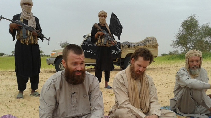 Three Western hostages taken captive in northern Mali almost nine months ago by the Qaida-linked Al-Din movement, appear in an undiscloed location in Mali.  (AFP Photo / Al-Jazeera / HO)