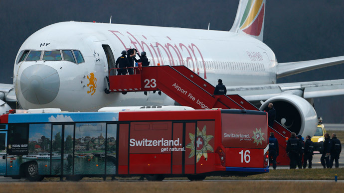 Police officers help a passenger disembark hijacked Ethiopian Airlines flight ET 702 at Cointrin airport in Geneva February 17, 2014.(Reuters / Denis Balibouse)