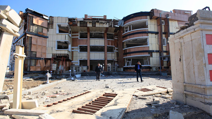 People gather at the site of a bomb attack at a damaged building of the Ministry of Youth and Sport in Baghdad's Bayaa District, February 18, 2014.(Reuters / Ahmed Saad )