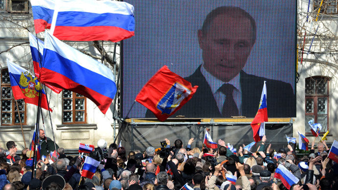 People wave Russian flags as they look at Russian President Vladimir Putin delivering a speech on a screen on March 18, 2014, in Sevastopol. (AFP Photo / Viktor Drachev)