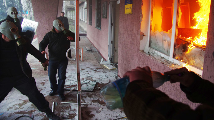 Anti-government  protesters wearing gas masks storm a regional police building as one prepares a petrol bomb in the eastern Ukrainian city of Horlivka (Gorlovka), near Donetsk, on April 14, 2014. (AFP Photo / Alexey Kravtsov)