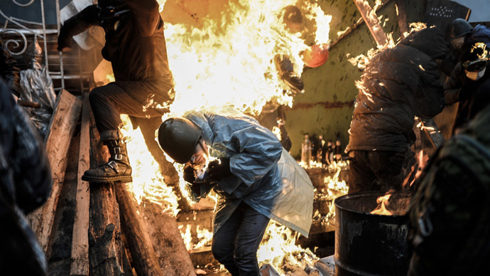Protesters burn as they stand behind burning barricades during clashes with police on February 20, 2014 in Kiev. (AFP Photo/Bulent Kilic)