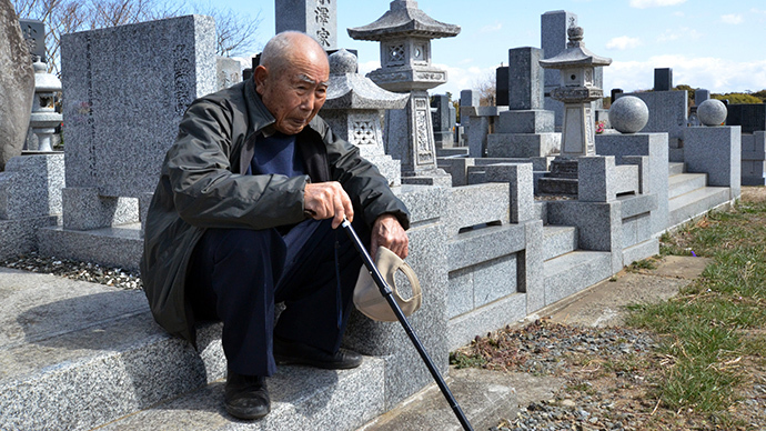 An elderly man sits as he and with his wife (not pictured) visit a cemetery to pay respects to their son who was killed in the March 2011 tsunami, in Minamisoma in Fukushima prefecture on March 11, 2013. (AFP Photo / Yoshkazu Tsuno)