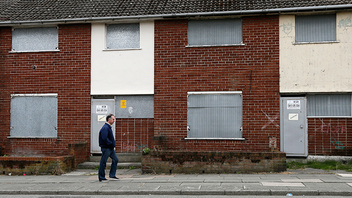 A man walks past boarded up houses in Liverpool, northern England (Reuters / Phil Noble)