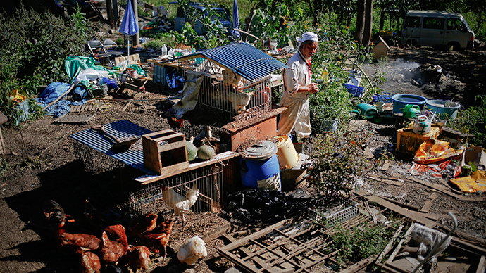 A man walks between cages with his over 500 animals he keeps at his home in the exclusion zone near Naraha in Fukushima prefecture (Reuters / Damir Sagolj)