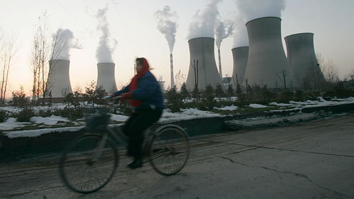 A woman rides her bicycle past the cooling towers of a power plant on the outskirts of Shijiazhuang, Hebei province (Reuters / Pillar Lee)