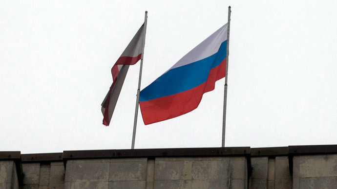 A Russian flag (R) is raised next to a Crimean flag on top of the Crimean parliament building in Simferopol February 27, 2014.(Reuters / Baz Ratner)