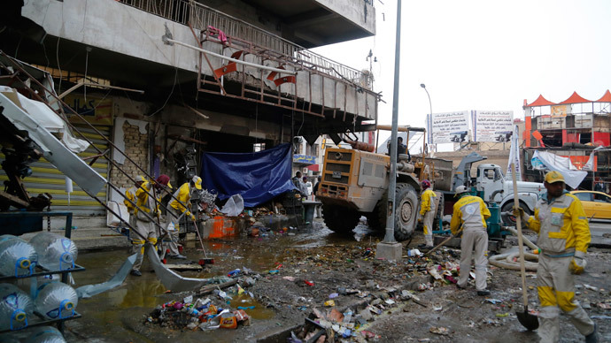 Municipal workers clean up the site of a car bomb attack in Baghdad's Karaada district February 26, 2014. (Reuters / Thaier al-Sudani)