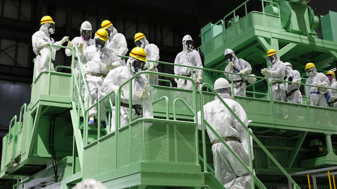 Members of the media and Tokyo Electric Power Co. (TEPCO) employees wearing protective suits and masks walk down the steps of a fuel handling machine on the spent fuel pool inside the No.4 reactor building at the tsunami-crippled TEPCO's Fukushima Daiichi nuclear power plant in Fukushima prefecture (Reuters/Kimimasa Mayama)