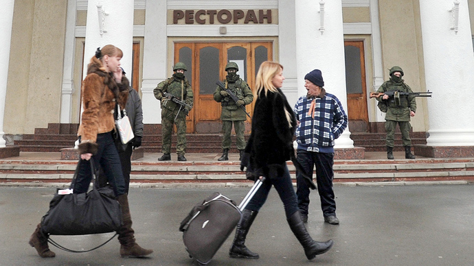 People walk in front of unidentified armed men patroling near the Simferopol airport on February 28, 2014 (AFP Photo / Genya Savilov)