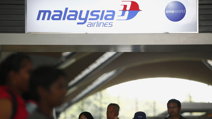 People walk under a Malaysia Airlines sign at Kuala Lumpur International Airport in Sepang March 8, 2014 (Reuters / Samsul Said)
