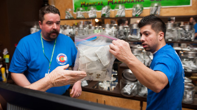 Sam Walsh, left, a budtender, and facility manager David Martinez set up marijuana products as the 3-D Denver Discrete Dispensary prepares to open for retail sales on January 1, 2014 in Denver, Colorado. (Theo Stroomer/Getty Images/AFP)