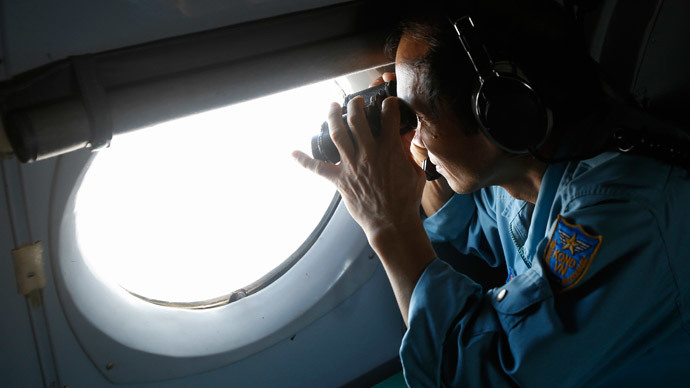 Military officer Pham Tuan Minh looks through a window of a Vietnam Air Force AN-26 aircraft during a mission to find the missing Malaysia Airlines flight MH370, off Con Dao island March 13, 2014.(Reuters / Kham)