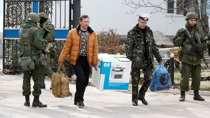 Men, believed to be Ukrainian servicemen, with belongings walk past armed men, while leaving the territory of the naval headquarters in Sevastopol, March 19, 2014. (Reuters / Vasily Fedosenko)