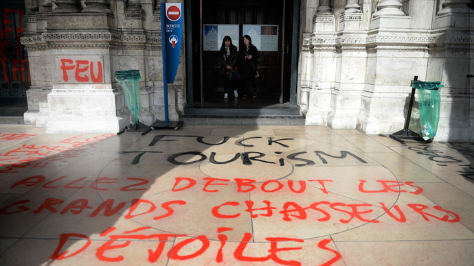 "People walk past grafittis reading ""Come on stand up great star hunters"" written on the Sacre-Coeur Basilica in the Montmartre area in Paris on March 19, 2014. (AFP Photo / Martin Bureau)"