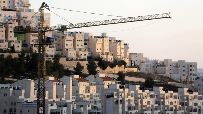 A crane is seen next to homes in a Jewish settlement near Jerusalem known to Israelis as Har Homa and to Palestinians as Jabal Abu Ghneim (Reuters/Ammar Awad)