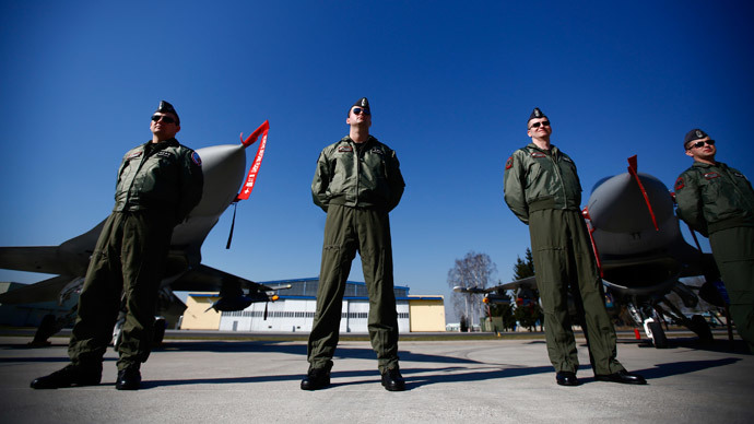 Polish pilots stand in front of F-16 fighter jets as Poland's President Bronislaw Komorowski (not pictured) visits at the Lask airbase in central Poland March 11, 2014.(Reuters / Kacper Pempel )