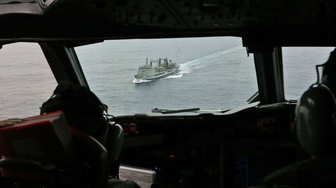 Australian Flight Lieutenant Jason Nichols (L), on board a Royal Australian Air Force AP-3C Orion, looks ahead towards the HMAS Success as they search for missing Malaysia Airlines flight MH370 debris or wreckage in the southern Indian Ocean on March 22, 2014. (AFP Photo / Pool / Rob Griffith)