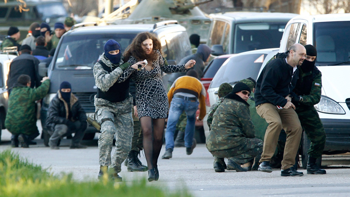 Civilians are led by members of Crimea's self-defence units as they run outside a military base during an assault in the Crimean town of Belbek near Sevastopol March 22, 2014 (Reuters / Vasily Fedosenko)