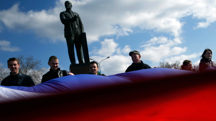 People hold a Crimean flag in front of Lenin's statue in the centre of Simferopol March 18, 2014 (Reuters / David Mdzinarishvili)