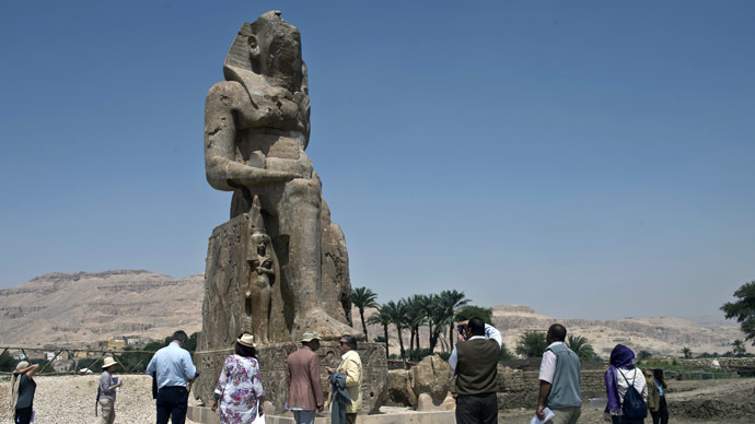 Tourists and journalists stand next to a newly displayed statue of pharaoh Amenhotep III and his wife Tiye (Down) in Egypt's temple city of Luxor on March 23, 2014. (AFP Photo)