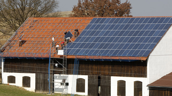 Workers install 320 square metres of solar panels on the roof of a farmstead barn in Binsham near Landshut, Germany (Reuters/Michaela Rehle)