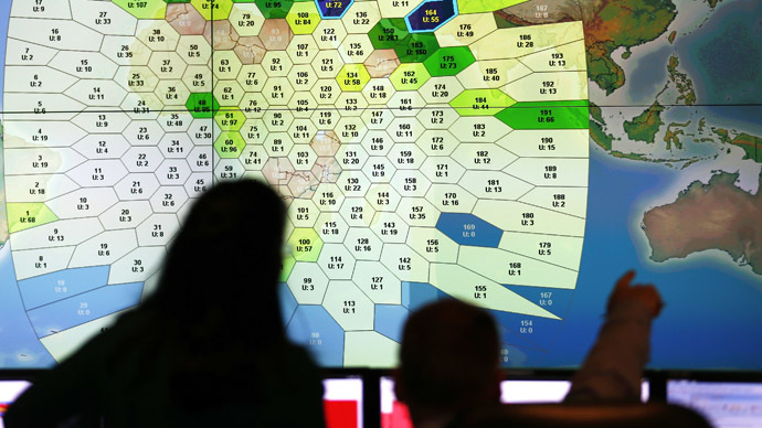 Staff at satellite communications company Inmarsat work in front of a screen showing subscribers using their service throughout the world, at their headquarters in London March 25, 2014. (Reuters/Andrew Winning)