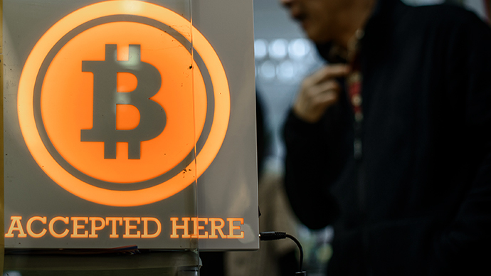A man walks out of a shop displaying a bitcoin sign (AFP Photo / Philippe Lopez)