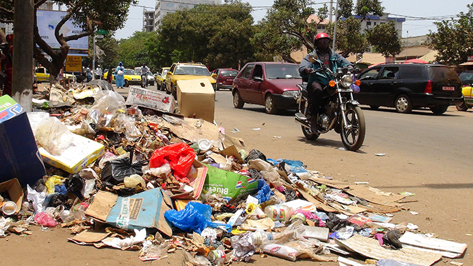 A motorcyclist rides past garbage strewn on the street in Conakry March 27, 2014. (Reuters / Saliou Samb)
