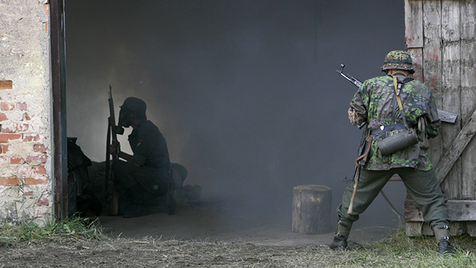 History enthusiasts re-enact a World War II battle scene between Soviet and German troops, in Ugale July 24, 2010. (Reuters /  Ints Kalnins)