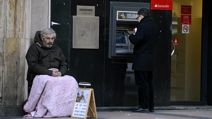 A begger sits beside an ATM in Madrid. (AFP Photo / Gerard Julien)