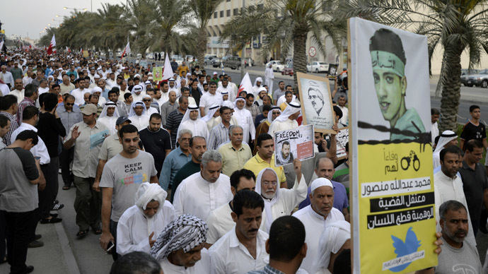 Protesters holding signs march during an anti-government rally organised by Bahrain's main opposition party Al Wefaq in Budaiya March 21, 2014. (Reuters)