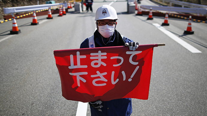 "A security personnel holds a flag, which reads ""Please Stop!"", as he stand by a steel gate that marks the border between Tamura and Okuma town in Okuma town, Fukushima prefecture April 1, 2014. (Reuters / Issei Kato)"