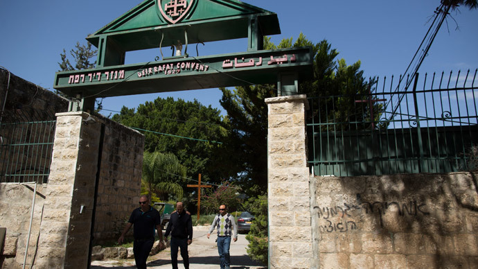 "People leave the Deir Rafat Catholic convent whose walls were sprayed with a graffiti (R) reading in Hebrew ""America is Nazi Germany"" on April 1, 2014 near the Israeli city of Beit Shemesh, west of Jerusalem.  (AFP Photo / Menahev Kahana)"