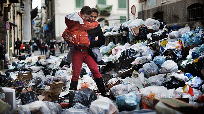 A mother carries her child through uncollected garbage on their way back from school in the historic Spanish district of Naples (AFP Photo / Roberto Salomone)