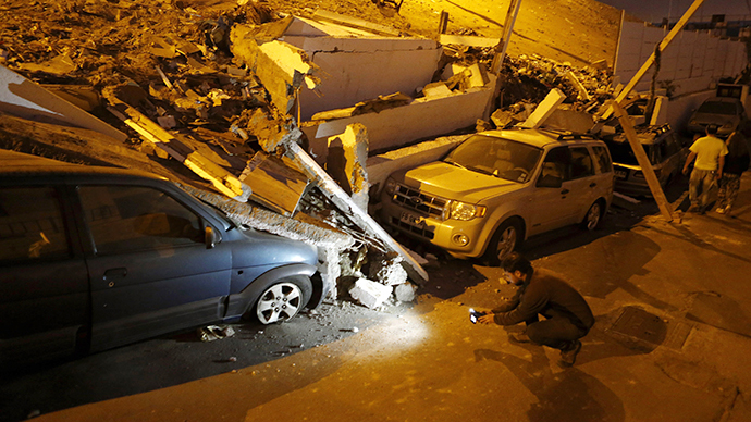 A cameraman records near cars caught under rubble after an earthquake and tsunami hit the northern port of Iquique April 2, 2014. (Reuters / Ivan Alvarado)