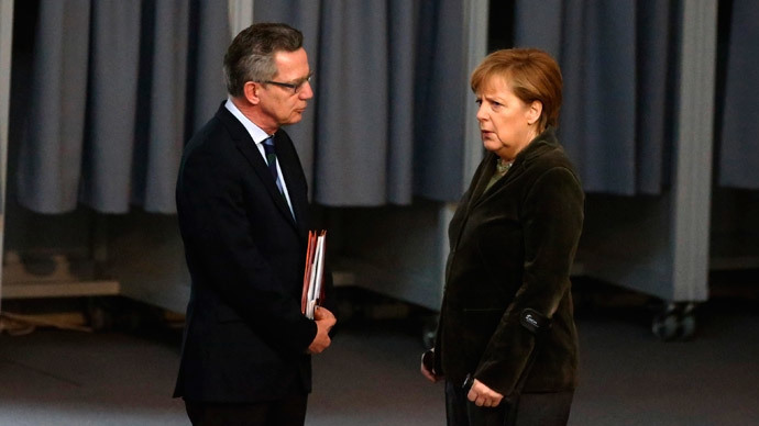 German Chancellor Angela Merkel (R) talks with Interior Minister Thomas de Maiziere before a session of the lower house of parliament, the Bundestag, in Berlin February 20, 2014.(Reuters / Thomas Peter)