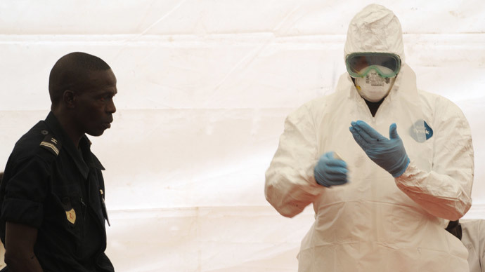 A Senegalese hygienist demonstrates how to protect oneself against the Ebola virus on April 8, 2014 at Dakar airport, during a visit of the Senegalese health minister to check the safety measures put in place to fight against the virus' spread in western Africa. (AFP Photo / Seyllou)
