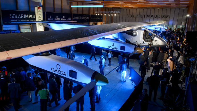 People look at the second Solar Impulse experimental solar-powered plane, the HB-SIB, to be used for a round-the-world voyage next year, during its presentation in Payerne on April 9, 2014 (AFP Photo / Fabrice Coffrini)